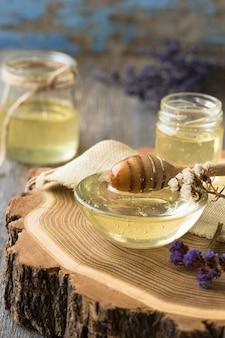 Pote de mel, concha, pote de mel fresco, favo de mel em uma mesa de madeira ao ar livre. mel com concha de sopa de mel na mesa de madeira