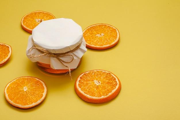 Pote de mel de close-up com fatias de laranja