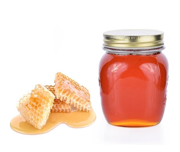 Pote de mel de favo de mel no fundo branco
