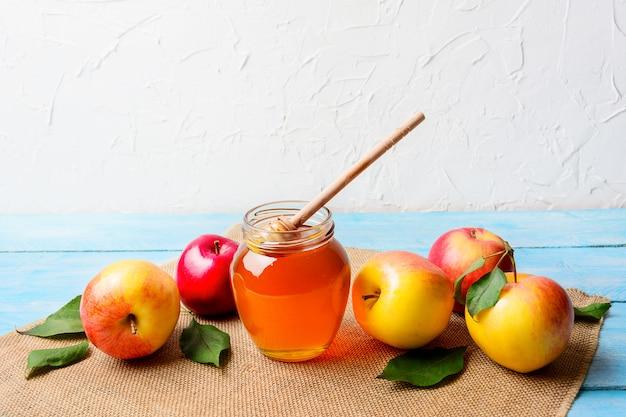 Pote de mel de vidro com dipper e maçãs copie o espaço