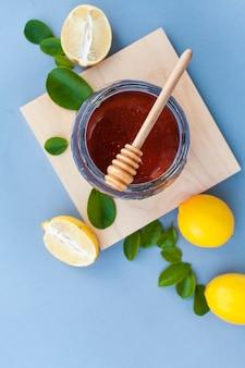 Pote de mel de vista superior em cima da mesa com limões