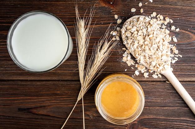 Pote de mel e copo de leite na mesa de madeira escura.