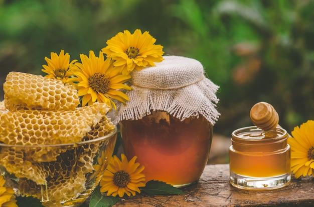Pote de mel e favo de mel na mesa de madeira. frasco e flores do mel em uma tabela de madeira e em um fundo verde da natureza. conceito de produto natural