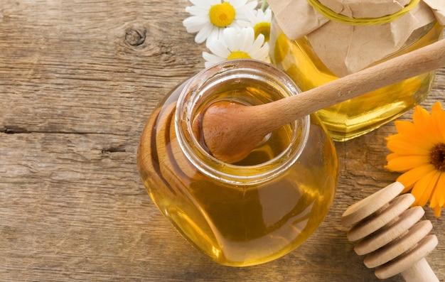 Pote de mel e flores em fundo de madeira