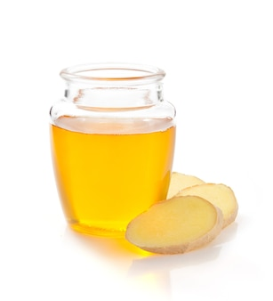 Pote de mel e gengibre isolado no fundo branco