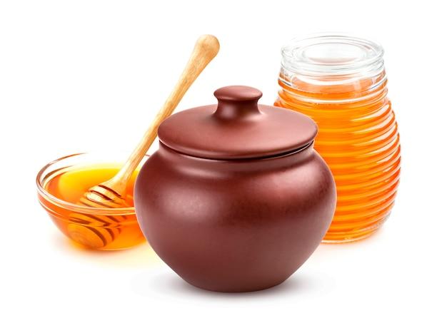 Pote de mel e jarra de vidro de mel isolado no branco