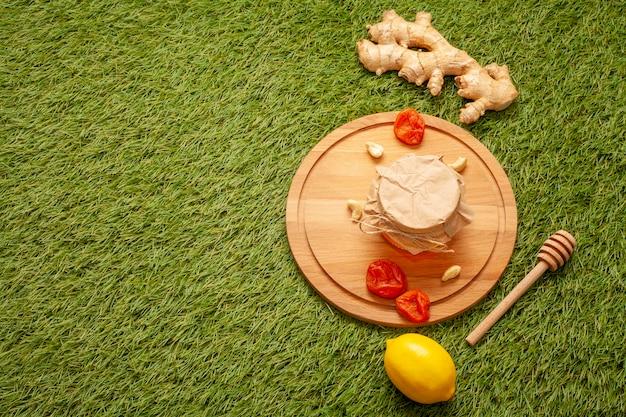 Pote de mel em uma placa de madeira e gengibre