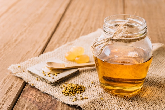 Pote de mel; sementes de pólen de abelha e doces em pano de saco
