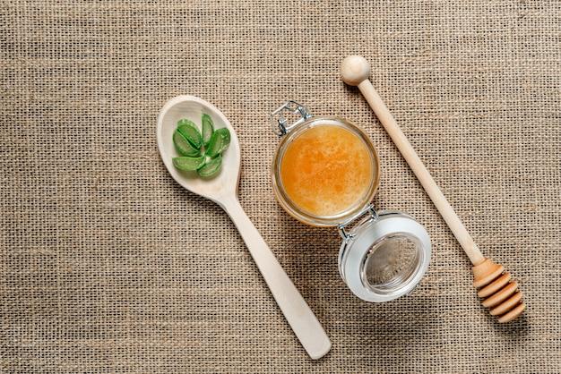 Pote de mel, uma colher de pau para mel e uma colher com folhas de aloe vera na serapilheira.
