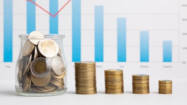 Pote de moedas ao lado de pilhas de moedas