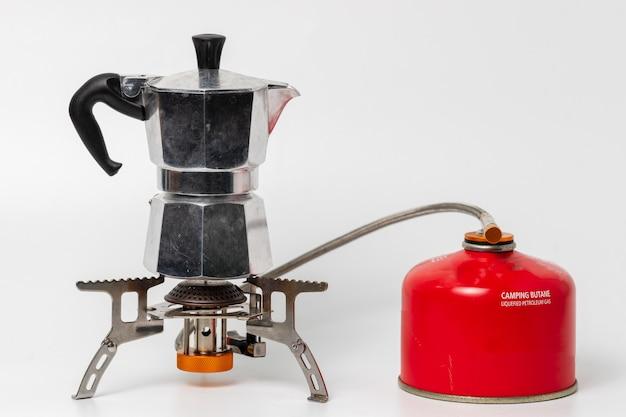 Pote de moka prata no fogão portátil com garrafa de butano de campismo vermelho