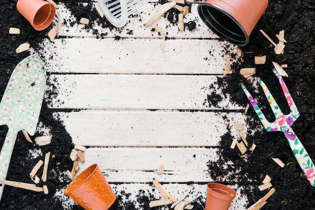 Pote de plástico marrom; equipamentos de jardinagem e solo acima da mesa de madeira