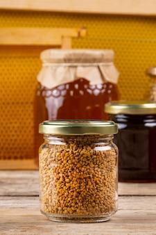 Pote de pólen com potes de mel e favo de mel