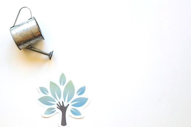 Pote de rega sobre a árvore de papel