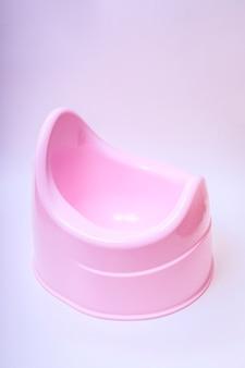 Pote de toucador para crianças pequenas. rosa potty em um fundo branco.