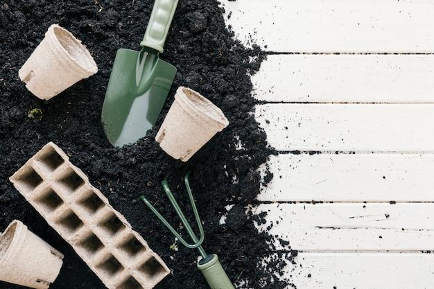 Pote de turfa e bandeja de turfa; terra preta com pá de jardinagem; ancinho de jardinagem sobre a mesa de madeira