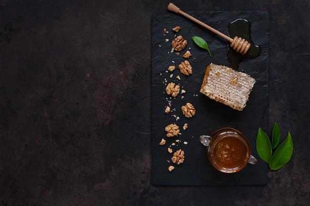Pote de vidro com mel natural fresco, favo de mel e nozes em uma placa de pedra.