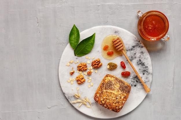 Pote de vidro com mel natural fresco, pão e nozes em uma placa de pedra.