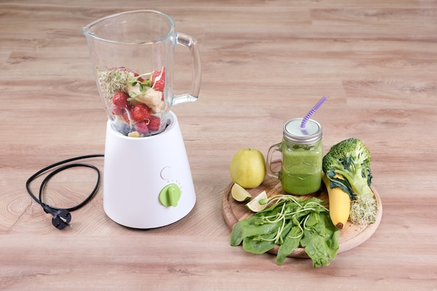 Pote de vidro de bebida dietética com brócolis, espinafre, microgreens, limão e banana e uma batedeira cheia de ingredientes em fundo de madeira