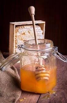 Pote de vidro de mel com uma colher de pau e favo de mel no fundo