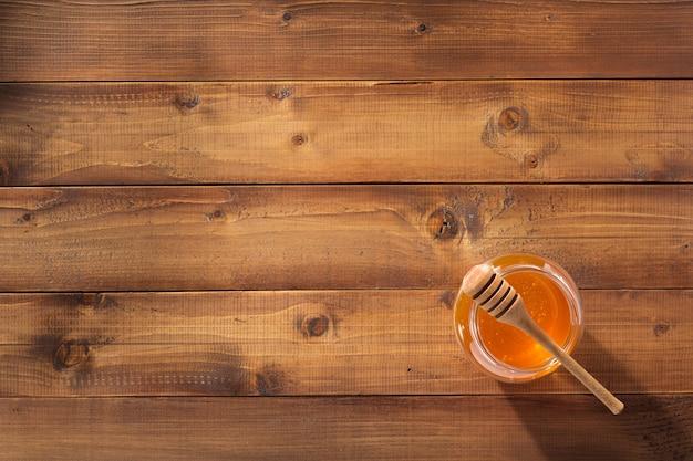 Pote de vidro de mel em fundo de madeira