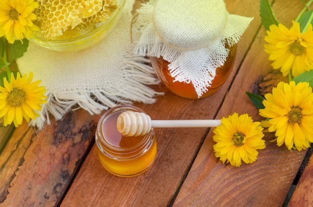 Pote e favo de mel na tabela de madeira. pote de mel e flowes na mesa