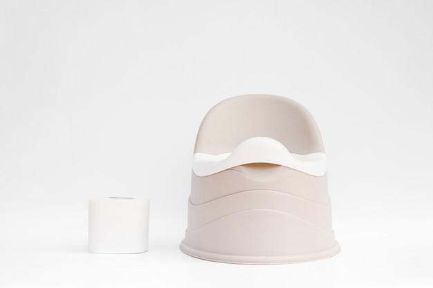 Pote infantil bege com bacia removível fica e ao lado de um rolo de papel higiênico