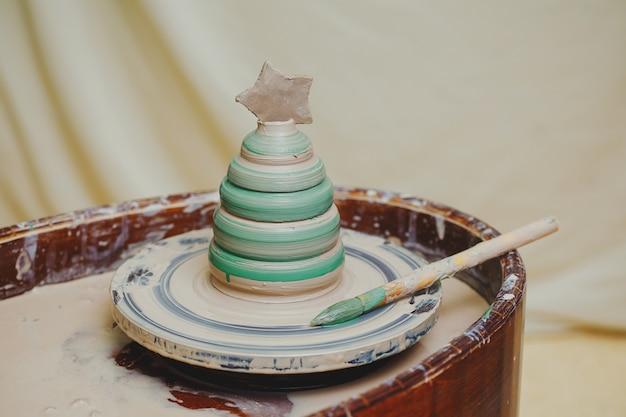 Pote pintado com forma de árvore de natal na roda de oleiro