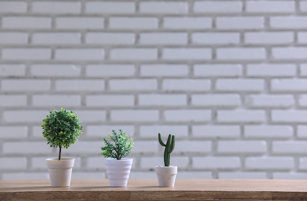 Pote verde na mesa de madeira com parede branca.