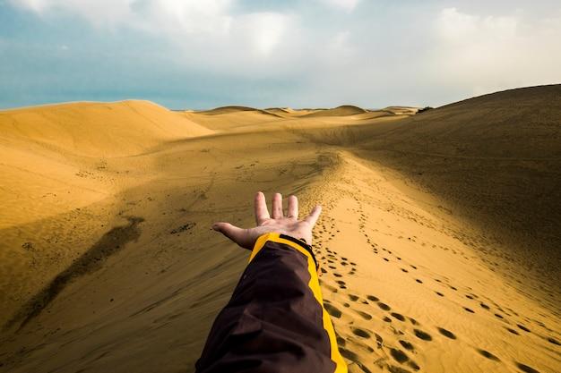 Potência, controle e exploração do conceito de viagens e sede de viagens com a mão do homem acima das dunas e do deserto em um lugar tropical. eu quero mover e viver a cena das fotos. pessoas e estilo de vida com liberdade