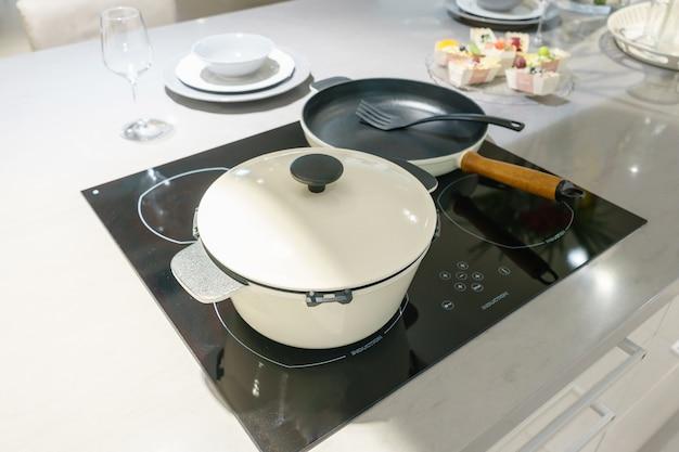 Potenciômetro do metal no hob da indução na cozinha moderna.