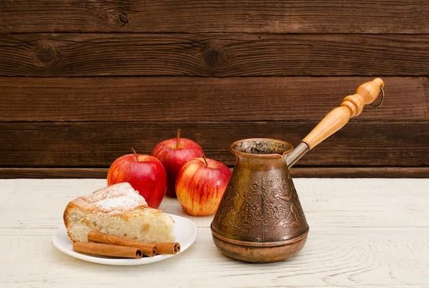 Potes de café, torta de maçã, paus de canela e maçãs maduras