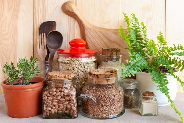 Potes de cereais, utensílios de cozinha e plantas domésticas. ambiente saudável, cozinha confortável, conceito de estilo de vida sustentável.