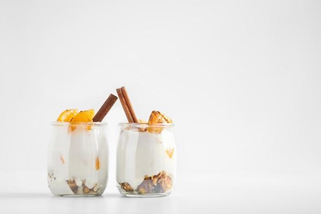 Potes de iogurte grego com granola, canela e damascos enlatados