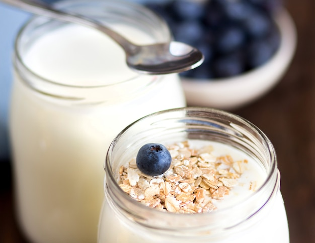 Potes de iogurte natural fresco e mirtilos em uma mesa de madeira escura close-up