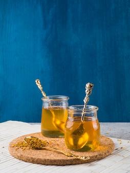 Potes de mel de vidro com colher na cortiça coaster