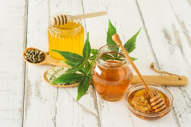 Potes de mel fresco de cbd com concha de mel em close-up de mesa de madeira com folhas de cânhamo.