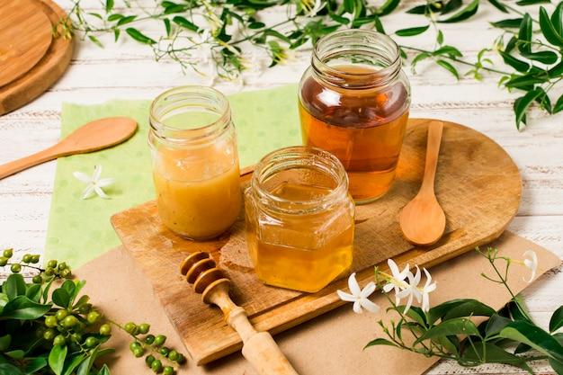 Potes de mel na mesa com folhas