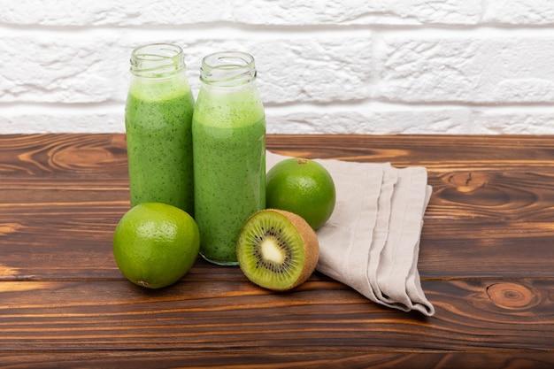 Potes de smoothie verde saudável com conceito de dieta de desintoxicação de espinafre fresco