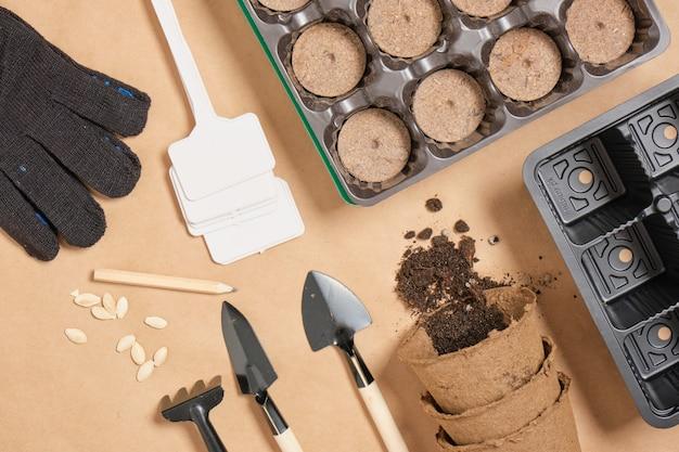 Potes de turfa, pás, potes, pratos e sementes de abobrinha na vista superior de papel artesanal, plantio de primavera, tudo para o crescimento de mudas