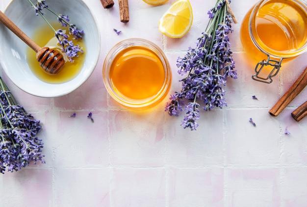 Potes e tigela com mel e flores frescas de lavanda em um fundo de ladrilho rosa