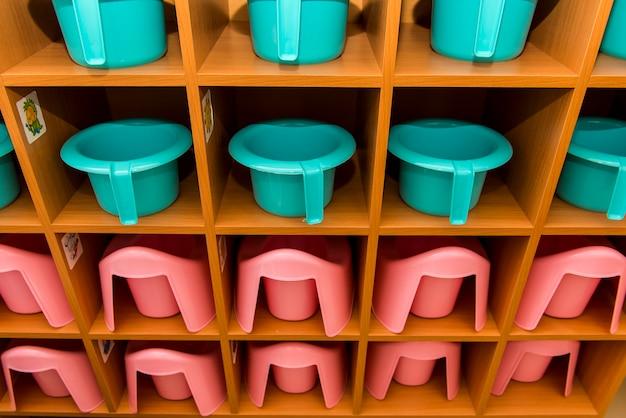 Potes infantis turquesa e rosa estão enfileirados no balcão do banheiro do jardim de infância
