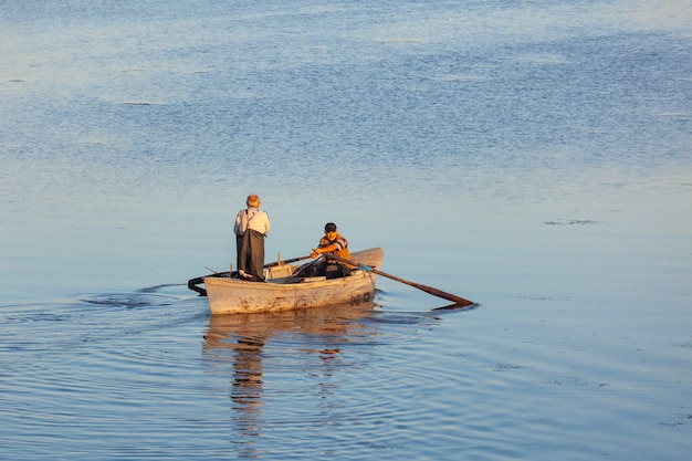 Poti, geórgia - 01.09.2019: um pequeno barco e os pescadores no lago em paliastomi. poti. natureza.