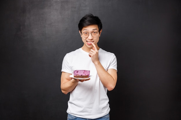 Potrait de cara tímido e bobo asiático sugerindo seu pedaço de bolo para a garota que ele gosta