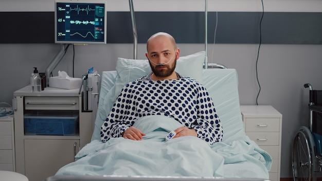 Potrait de homem doente descansando na cama à espera de tratamento respiratório se recuperando após cirurgia médica na enfermaria do hospital. paciente hospitalizado olhando para a câmera usando tubo de oxigênio nasal