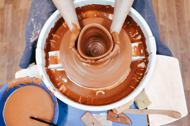 Potter atrás da roda do oleiro forma argila para criar pratos de cerâmica