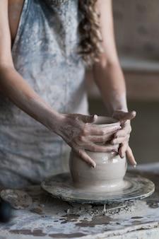 Potter esculpe um vaso na roda de oleiro