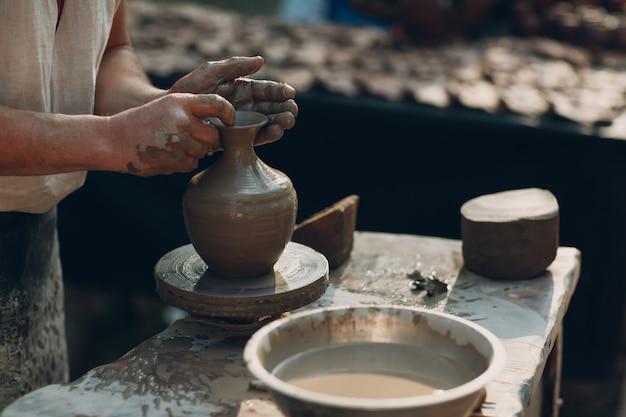 Potter faz jarra de barro na roda de oleiro