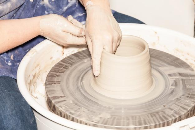 Potter feminino criando um pote de barro na roda de um oleiro