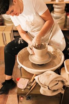 Potter feminino está alisando a superfície externa da panela na roda de oleiro